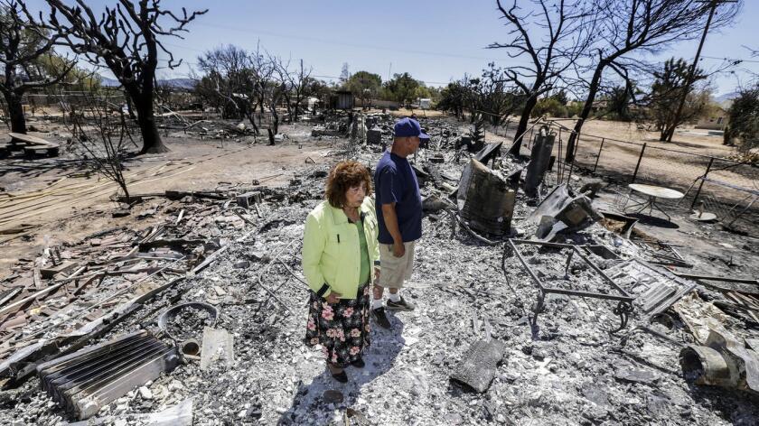Miguel y Mabel Ramos, ambos de 73 años, observan la devastación que dejo el incendio Blue Cut fire, después de pasar sobre las residencias de Oak Hills.
