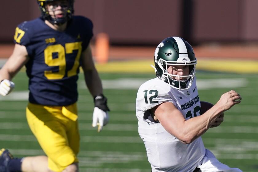 Michigan State quarterback Rocky Lombardi (12) scrambles during the second half of an NCAA college football game against Michigan, Saturday, Oct. 31, 2020, in Ann Arbor, Mich. (AP Photo/Carlos Osorio)