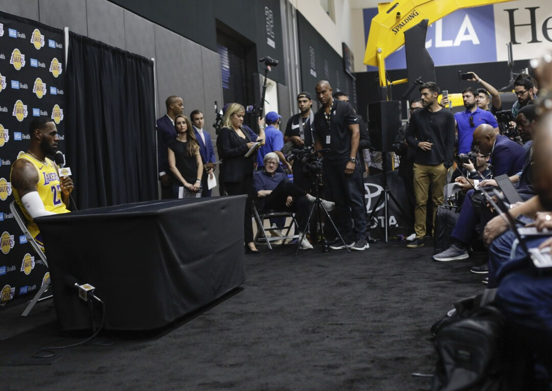 LeBron James, in Lakers uniform, sits behind a table holding a microphone. Media members are packed nearby.
