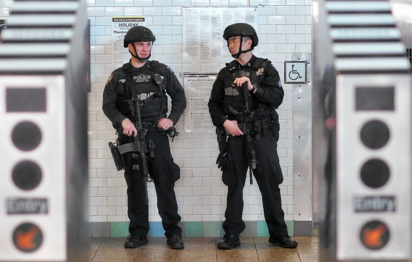 New York police officers guard a subway entrance at Times Square on Wednesday, five days after the Paris attacks.