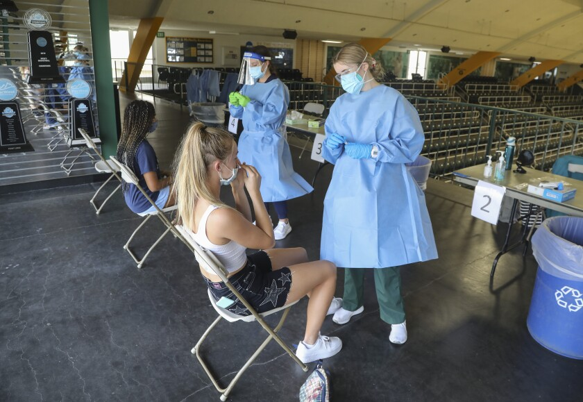 Workers in blue gowns and masks prepare to give coronavirus swab tests to two women in a college gymnasium