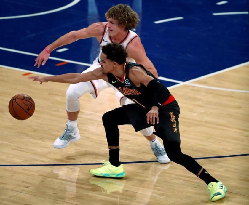 El jugador Ron Baker (i) de New York Knicks en acción ante Trae Young (d) de los Atlanta Hawks, durante un juego de la NBA el pasasdo 17 de octubre. EFE