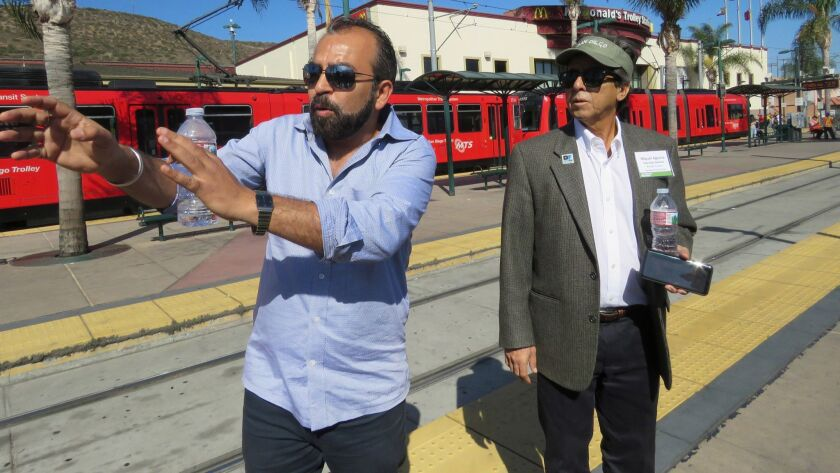 As San Ysidro property owner Miguel Aguirre d listens, merchant Sunil Gakhreja, the owner of Sunnyâ€