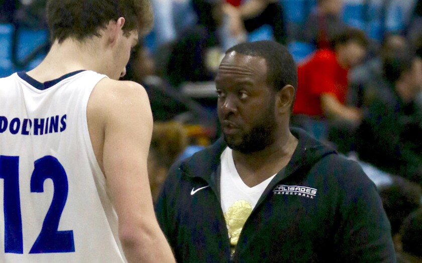 Palisades coach Donzell Hayes talks to forward Caden Arnold.