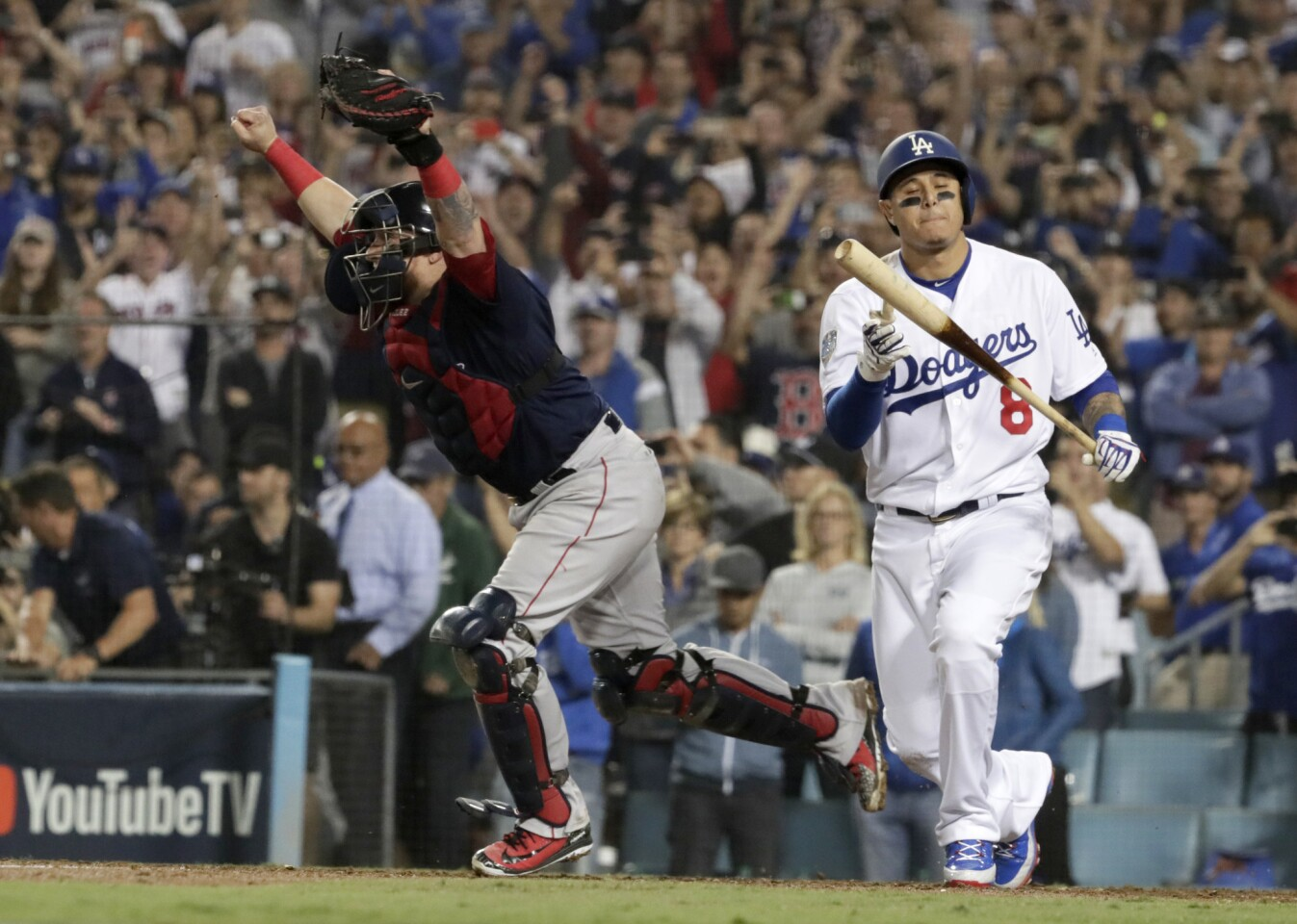 Dodgers' Manny Machado strikes out as Red Sox catcher Christian Vazquez charges to the mound to celebrate winning the 2018 Word Series.