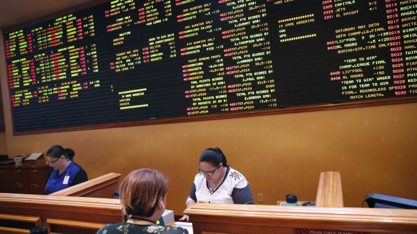 Crystal Kalahiki, right, takes a bet in the sports book at the South Point hotel-casino, Monday, May 14, 2018, in Las Vegas.
