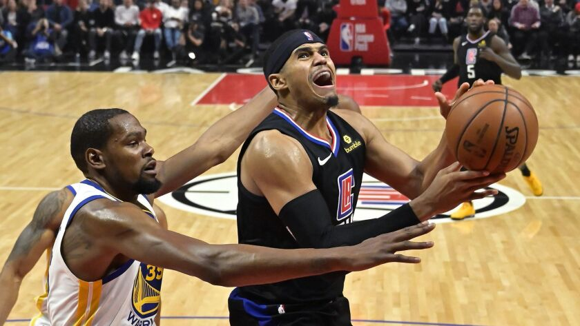 Clippers forward Tobias Harris, right, drives for a layup against Golden State Warriors forward Kevin Durant during the second half on Jan. 18, 2019, at Staples Center.