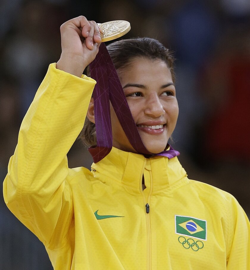 FILE - In this July 28, 2012, file photo, Sarah Menezes, of Brazil, holds up her gold medal in the women's 48kg judo competition at the 2012 Summer Olympics in London. When the judo events kick off at the Rio de Janeiro games, the home team will send out a defending Olympic champion on the first da