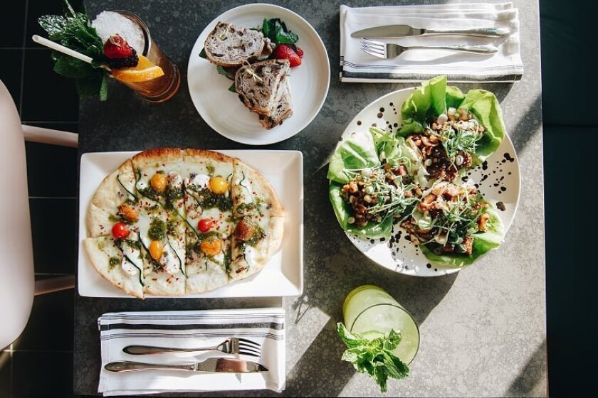 A selection of dishes, including a flatbread and lemongrass tofu lettuce wraps at Clara restaurant and bar, which opened Sept. 1 in the Carlsbad Village Faire center in Carlsbad.