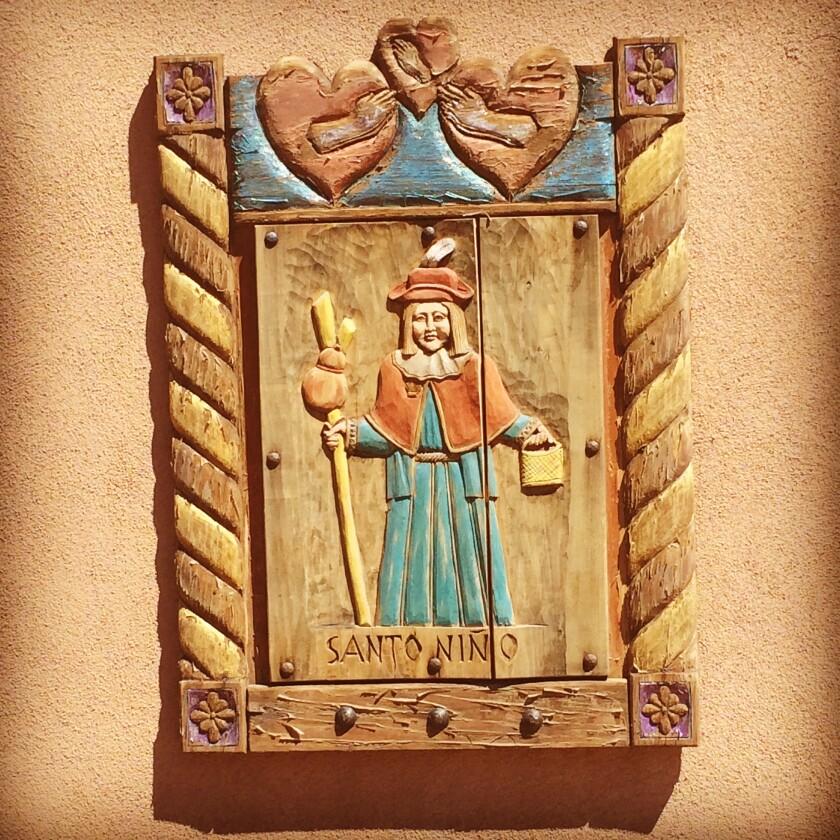A wooden plaque featuring the Santo Niño de Atocha at the Santuario de Chimayó in New Mexico.