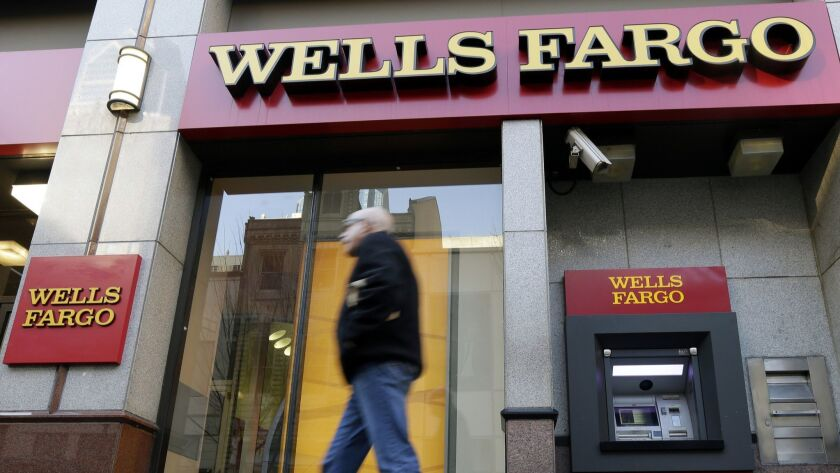 FILE - In this Dec. 19, 2012, file photo, a man walks past a Wells Fargo branch in Philadelphia. Wel