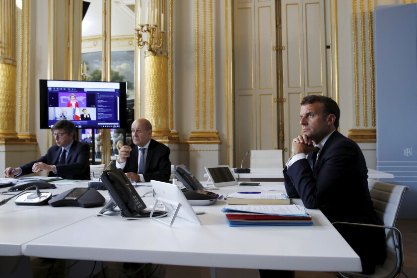 French President Emmanuel Macron, right, listens as he attends with French Foreign Minister Jean-Yves le Drian, center, an international video-conference on coronavirus vaccination at the Elysee Palace in Paris, on Monday.