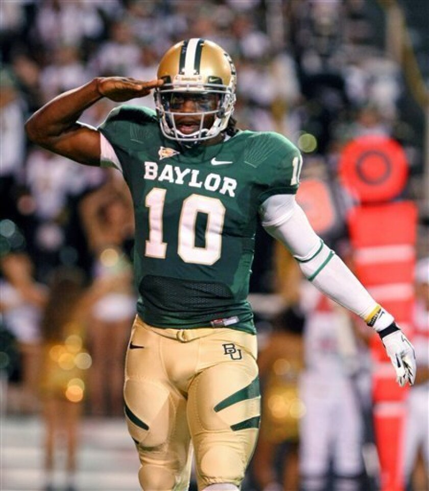FILE - In this Oct. 8, 2011, file photo Baylor quarterback Robert Griffin III salutes after throwing a touchdown pass to wide receiver Kendall Wright during an NCAA college football game in Waco, Texas. A person familiar with the decision says Heisman Trophy winner Griffin has decided to enter the NFL draft. ESPN, citing an anonymous family source, first reported that Griffin is going pro and is in the final stages of picking an agent. (AP Photo/Waco Tribune-Herald, Jerry Larson, File)