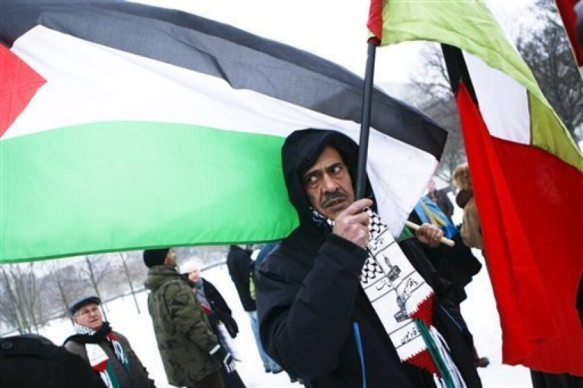 Men with Palestinian flags attend a protest against the Israeli government near the chancellery in Berlin, Germany, Monday, Jan. 18, 2010. Israel's government convened for the first time in Berlin, the former heart of the Nazi regime, for a special joint session with the German government highlight