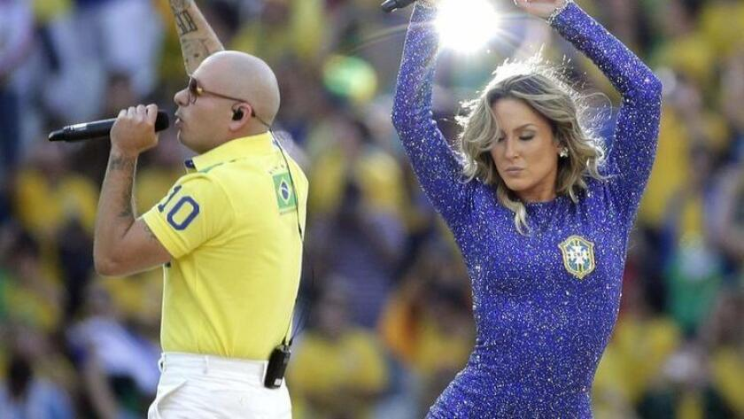 Rapper Pitbull, left, and Brazilian singer Claudia Leitte perform during the opening ceremony ahead of the group A World Cup soccer match between Brazil and Croatia, the opening game of the tournament, in the Itaquerao Stadium in Sao Paulo, Brazil, Thursday, June 12, 2014. (/ (AP Photo/Felipe Dana) The Associated Press)