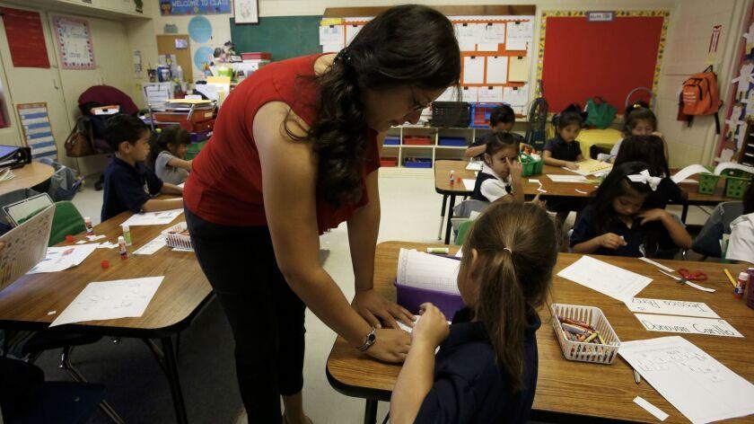 Kindergarten teacher Claudia Garcia helps Michelle Lopez at a Magnolia charter school in Northridge in 2014.