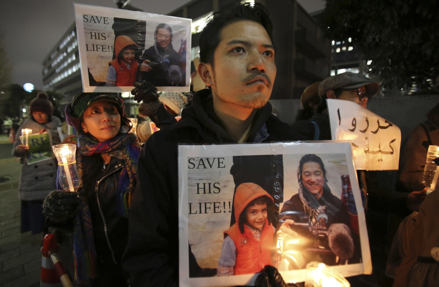 Protesters hold signs bearing Japanese journalist Kenji Goto who was taken hostage by the Islamic State group appeal the government to save Goto during a rally in front of the prime minister's official residence in Tokyo.