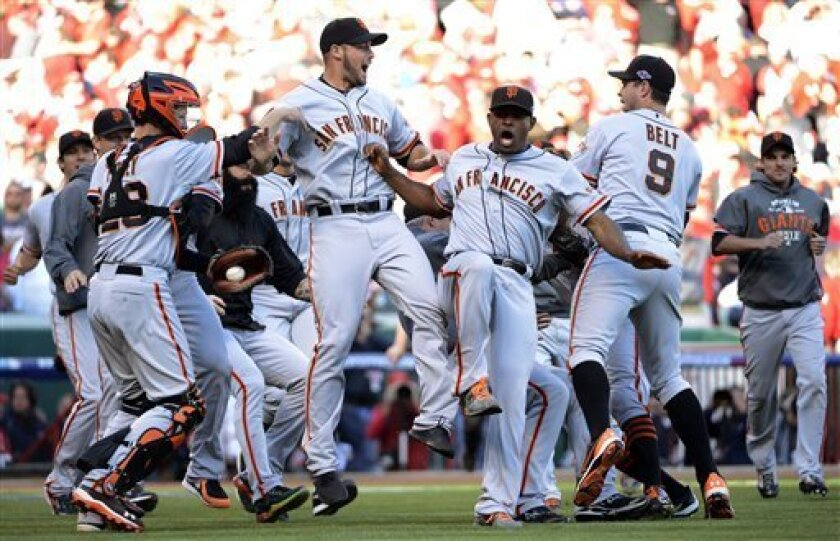 The San Francisco Giants celebrate after they defeated the Cincinnati Reds 6-4 in Game 5 of the National League division baseball series, Thursday, Oct. 11, 2012, in Cincinnati. The Giants won the final three games, all in Cincinnati, and advanced to the NL championship series. (AP Photo/Michael Keating)