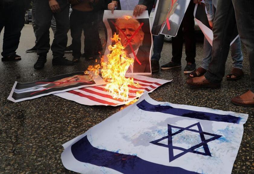 La delegación palestina en Naciones Unidas y sus aliados quieren impulsar una resolución del Consejo de Seguridad de la ONU en contra de la decisión estadounidense de reconocer Jerusalén como capital de Israel, dijeron hoy fuentes diplomáticas. Varios palestinos queman una bandera estadounidense y de israel, e imágenes del presidente de EE.UU., Donald Trump, y del primer ministro israelí Benjamin Netanyahu, durante una protesta contra el reconocimiento de Jerusalén como capital de Israel por parte de Trump y su orden de que se traslade allí la embajada estadounidense. EFE/ARCHIVO