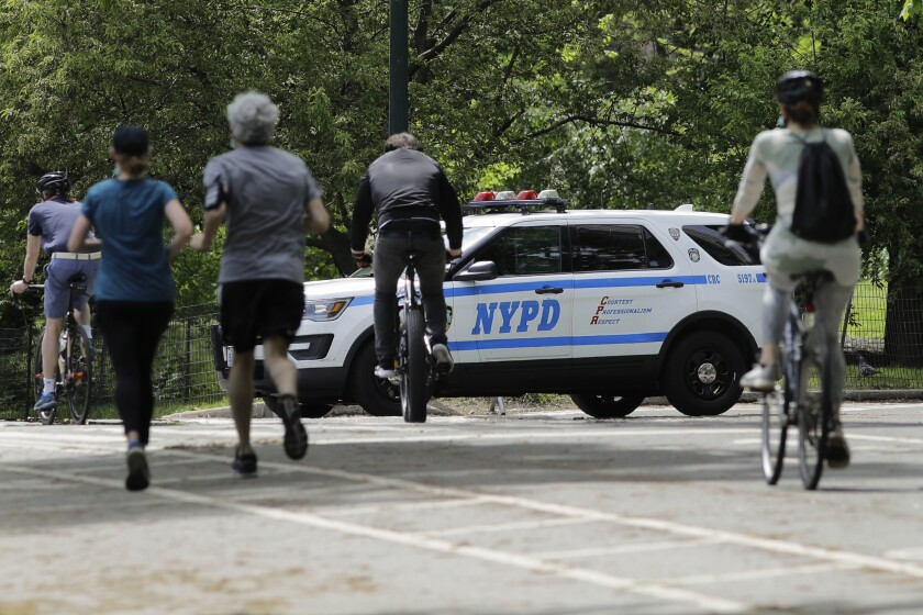 Runners and cyclists pass a New York police vehicle in Central Park on Saturday.