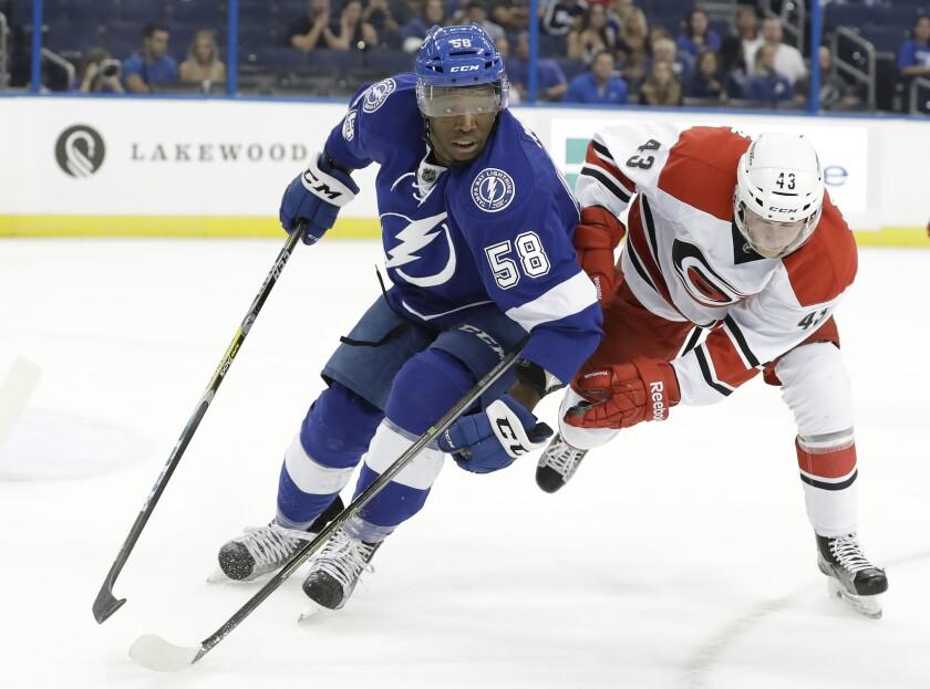 Tampa Bay Lightning forward Bokondji Imama, left, and Carolina Hurricanes forward Erik Karlsson chase after the puck.