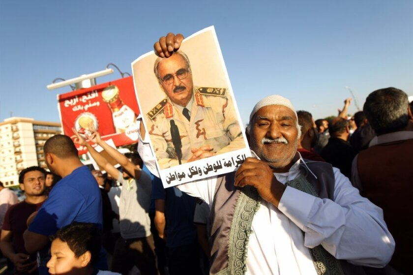 """A Libyan man is seen last week carrying a portrait of Khalifa Haftar during a rally in Benghazi in support of the rogue former general whose forces have launched a """"dignity"""" campaign to crush jihadist militias."""