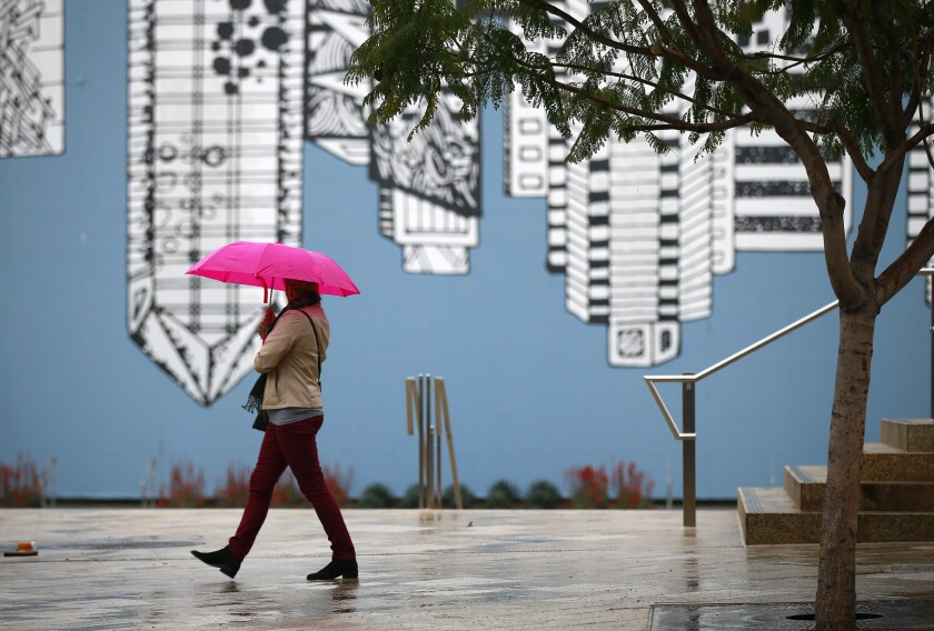 A woman walks in the rain in Horton Plaza Park on March 11, 2019.