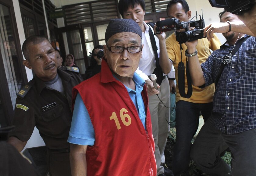 Japanese national Masaru Kawada, center, is mobbed by the media upon arrival for his sentencing hearing at the district court in Pariaman, West Sumatra, Indonesia Wednesday, May 20, 2015. Kawada was sentenced to life in prison for smuggling 2.35 kilograms (5.18 lbs) of crystal methamphetamine into the country in November 2014. (AP Photo/Rivo Andries)