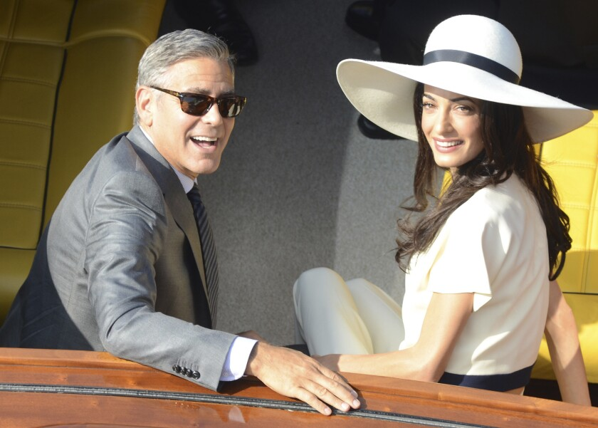 George Clooney, 53, and his new wife, Amal Alamuddin, 36, leave city hall after their civil marriage ceremony in Venice, Italy, on Monday.