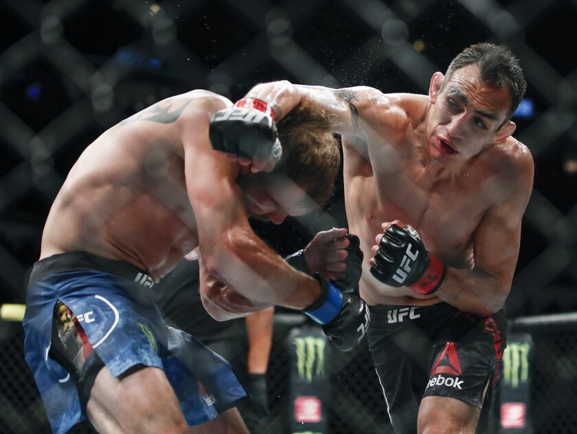 Tony Ferguson delivers a blow to Donald Cerrone during a lightweight fight at UFC 238 in Chicago on June 8, 2019.
