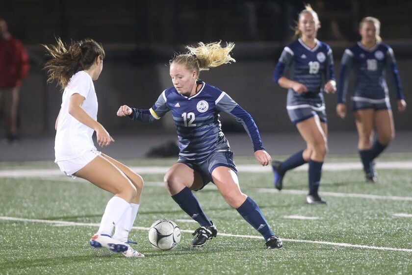Newport Harbor's Emily Johnson (12) dribbles past a Los Alamitos defender during girls' quarterfinal