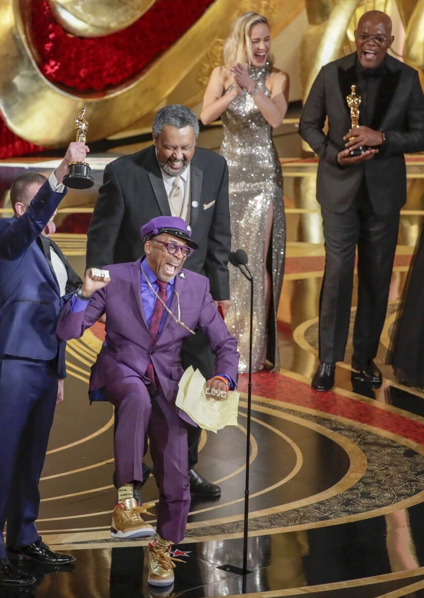 Spike Lee, in purple suit, reacts joyously after winning his first Oscar, presented by Brie Larson and Samuel L. Jackson, off to the right.