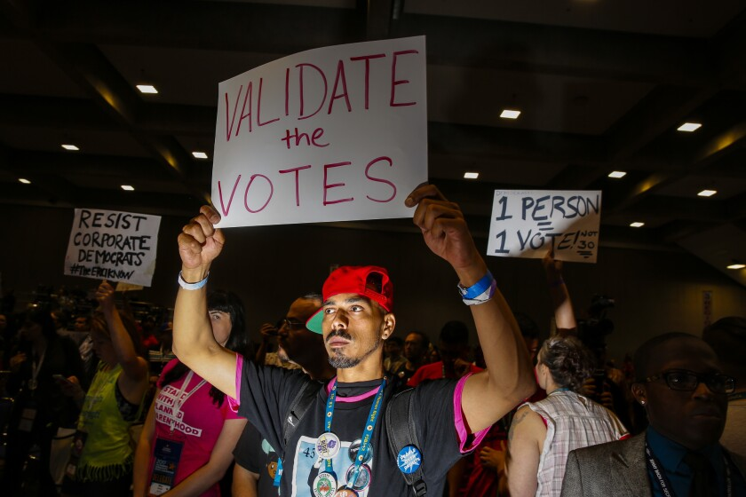 Gilbert Feliciano, center, and other delegates supporting Kimberly Ellis chant for an opportunity to speak during a contentious moment discussing the election results for California Democratic Party chairperson on the final day of the party's state convention.