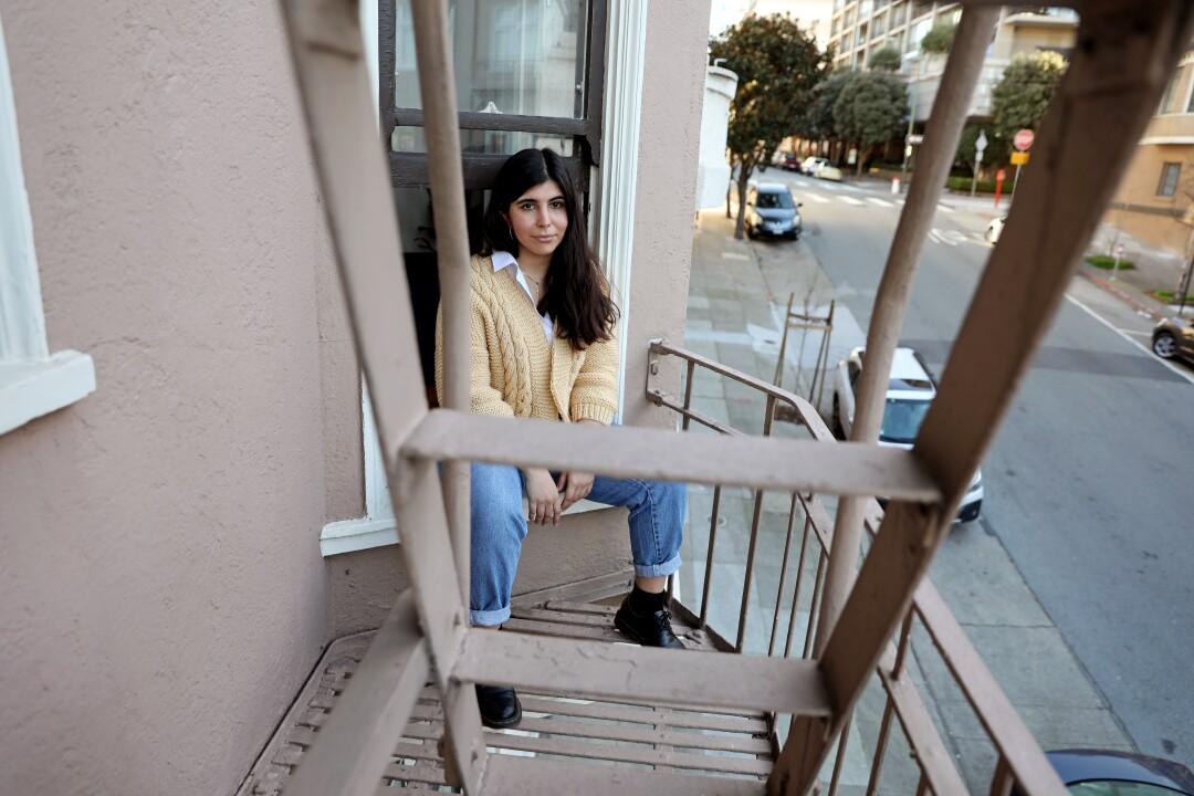 Sarah Abdeshahian sits on the window sill of her apartment.
