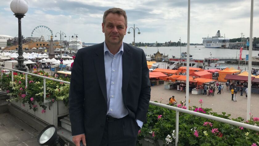 Helsinki Mayor Jan Vapaavuori stands on a balcony of City Hall overlooking the Finnish capital's market square and waterfront.