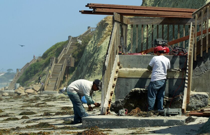 Daniel Pacheco, left, and Jimmy Jimenez repair a staircase at San Elijo State Beach. The nonprofit Friends of Cardiff and Carlsbad State beaches are repairing nine staircases in the area.