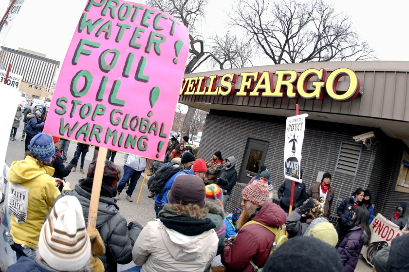 Dakota Access Pipeline protesters sing, pray and demonstrate Thursday at a Wells Fargo Bank branch in Bismarck, N.D.