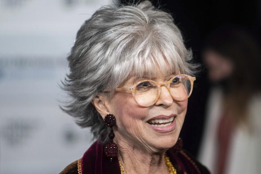 A closeup of Rita Moreno wearing light-rimmed glasses at a movie premiere