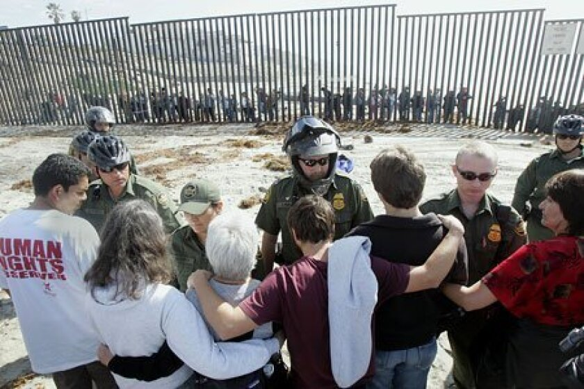 Demonstrators locked arms yesterday when they encountered Border Patrol agents who blocked access to the plaza known as Friendship Park. (Eduardo Contreras / Union-Tribune)