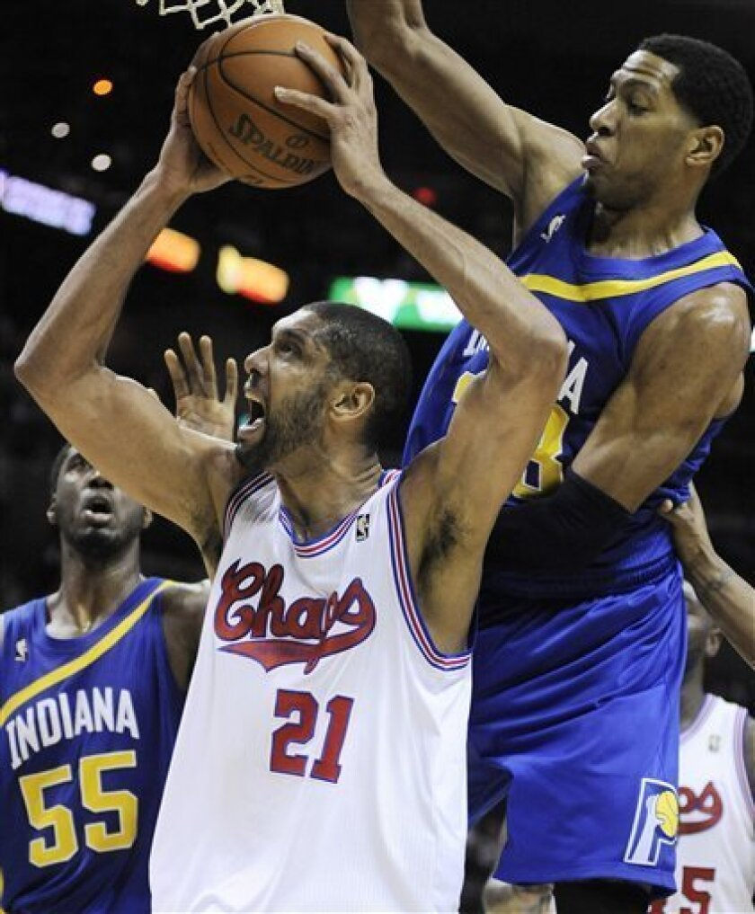 San Antonio Spurs' Tim Duncan (21) is defended by Indiana Pacers' Danny Granger, right, and Roy Hibbert during the second half of an NBA basketball game on Saturday, March 31, 2012, in San Antonio. (AP Photo/Darren Abate)