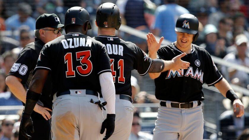 Miami Marlins' Marcell Ozuna, left, and J.T. Realmuto, right, congratulate Justin Bour, center, for
