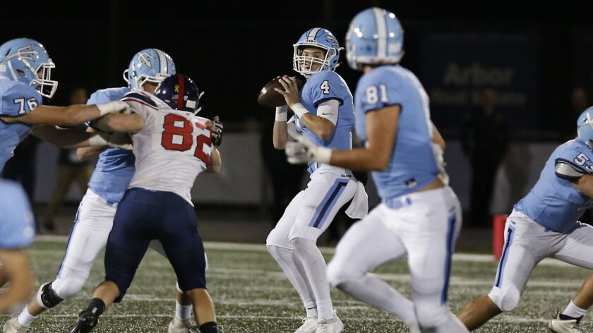 Corona del Mar quarterback Ethan Garbers (4) spots tight end Mark Redman (81) downfield during a playoff game on Nov. 10.