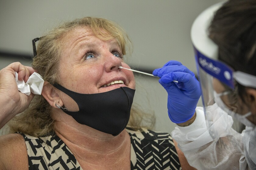 Laurie Goldfinger, left, attendance secretary at Agoura High School, takes a coronavirus test in Calabasas.