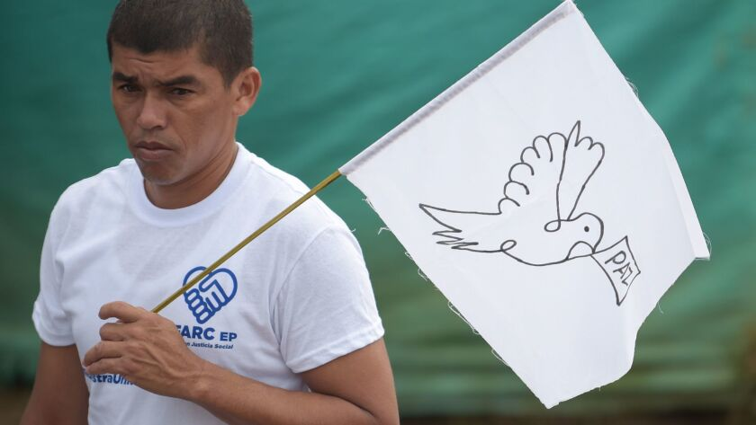 """A FARC rebel carries a flag with the word """"peace."""""""
