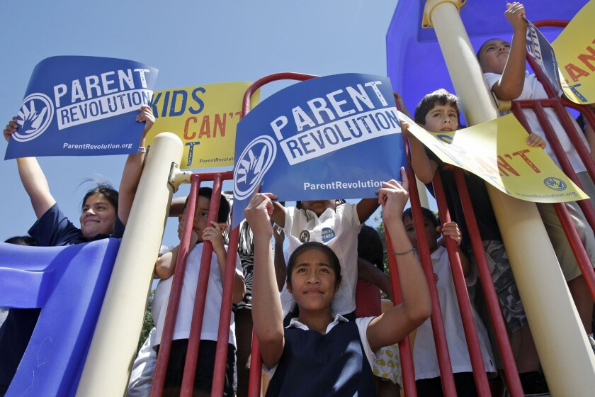 "Children hold up ""Parent Revolution"" signs during a press conference held next to Desert Trails Preparatory Academy in Adelanto in 2013. Parents used a state law to transform their local low-performing public elementary school into a not-for-profit charter campus."