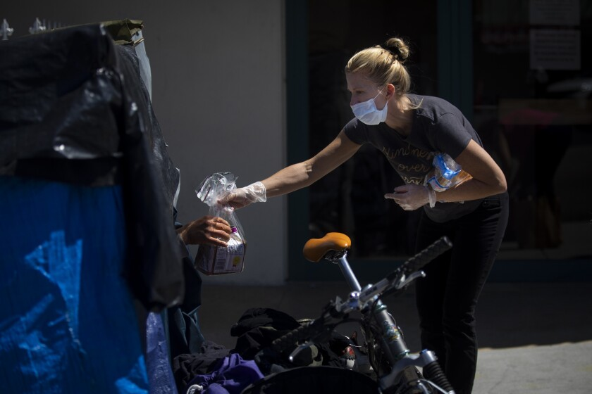 Heidi Roth, a registered nurse, hands bread to a man living in an encampment on a Los Angeles sidewalk. She and others are asking if anyone is experiencing coronavirus symptoms.