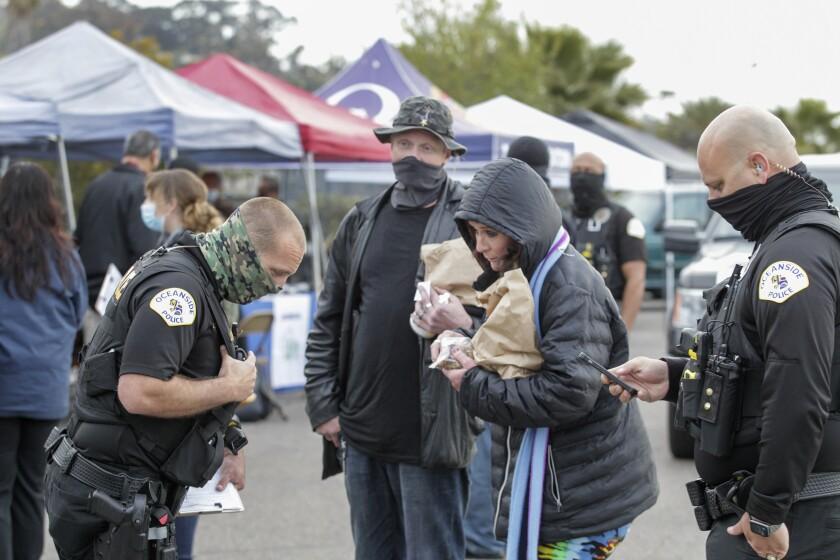 Jennifer Powers and R. Brett Powers, who are homeless, speak with Oceanside Police Officer Jerimy Stephens.