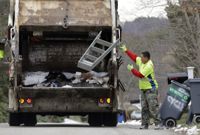 A sanitation worker throws a stepladder into his truck in North Andover, Mass., on March 23. On Friday, April 1, the government issued the U.S. jobs report for March.