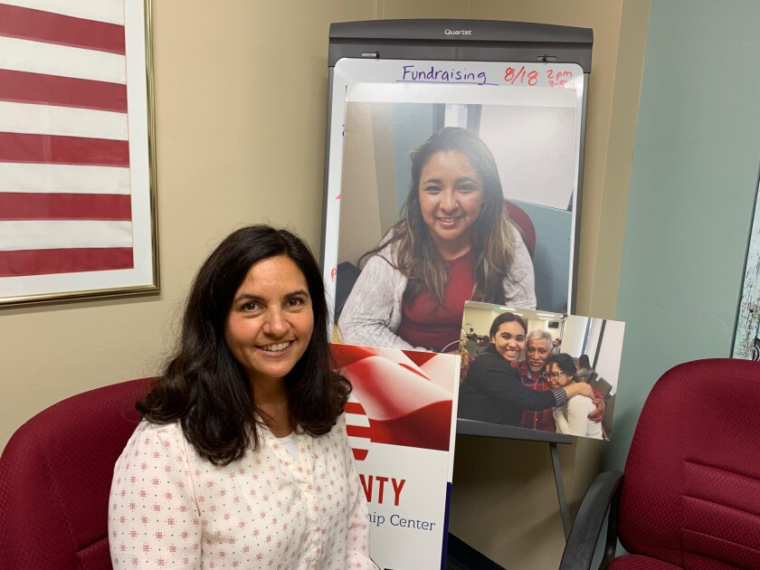 Executive Director Linda Martinez Haley of the North County Immigration & Citizenship Center in Solana Beach is seen in her office with photos of clients of the center who have been helped by its efforts.