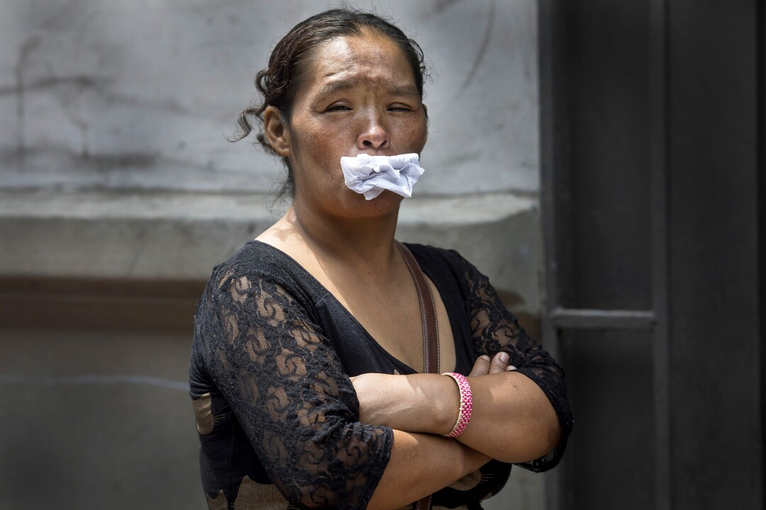 PERU: A woman stuffs paper into her mouth, her alternative to a face mask, as she waits in line for a free lunch from a charity organization that helps the homeless in Lima.